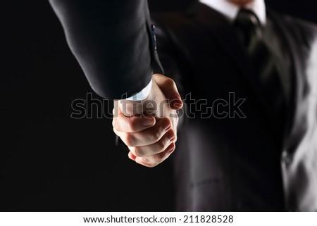 Handshake - Hand holding on black background - stock photo