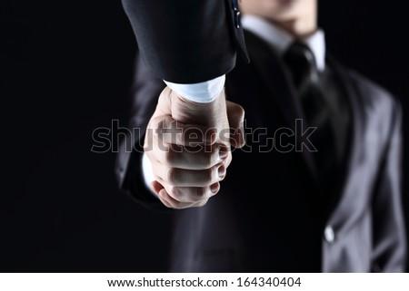 Handshake - Hand holding on dark background - stock photo