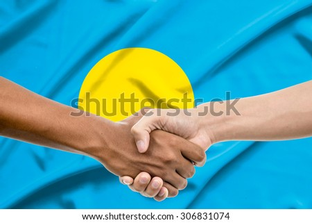 Handshake - Hand holding on palau flag background - stock photo