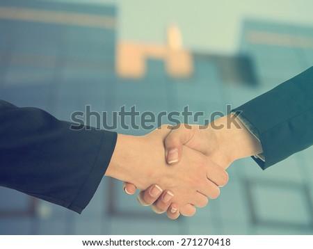 Handshake Handshaking and blured building in background - stock photo