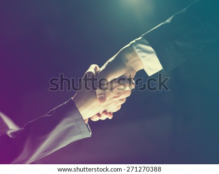 Handshake Handshaking light and dark - stock photo