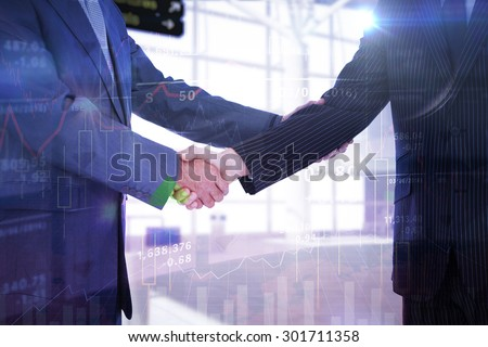 Handshake in agreement against stocks and shares - stock photo