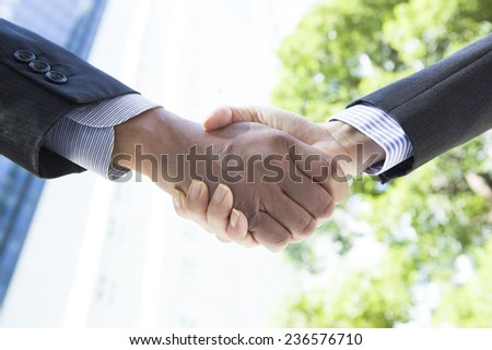 Handshake in business district - stock photo