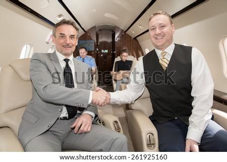 Handshake in corporate private jet - stock photo