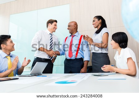 Handshake in diversity business team meeting, documents and graphs on the desk - stock photo