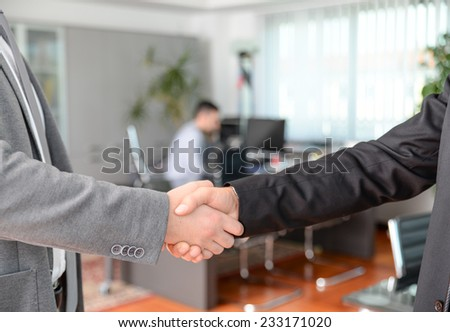 Handshake in the office - Business man working on computer desk - stock photo