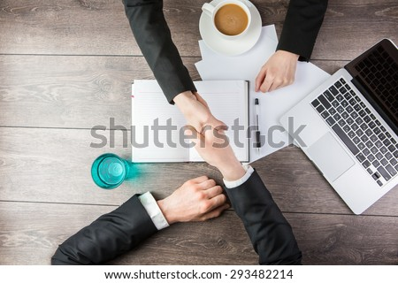 Handshake - Man and woman Hand holding. Top view for top managers - stock photo