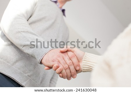 Handshake of adult man and young woman - stock photo