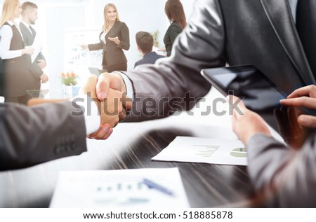 handshake of business partners after discussion of the financial