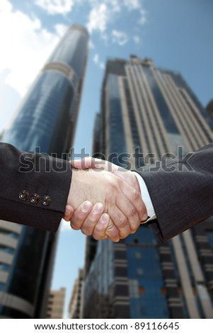 Handshake of business partners, against the backdrop of the city. - stock photo