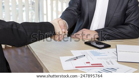 Handshake of business partners. Business background with some charts and office supplies on the table - stock photo