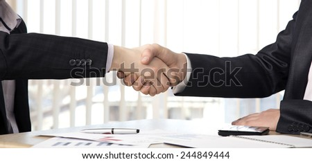 Handshake of business partners. Hands of casually dressed males. Business background with some charts and office supplies on the table. - stock photo