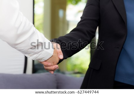 Handshake of businessman and businesswoman after successful business meeting.