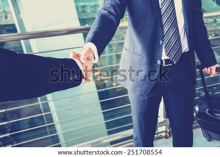 Handshake of businessman at the airport, business travel concept - vintage color effect - stock photo