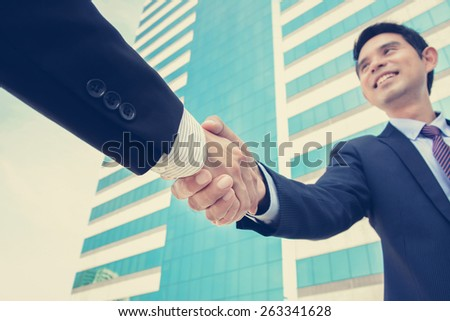Handshake of businessmen, greeting,dealing & partnership concepts - vintage tone - stock photo