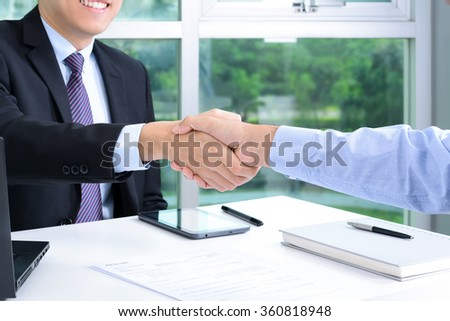 Handshake of businessmen in the office - making agreement and dealing concepts - stock photo