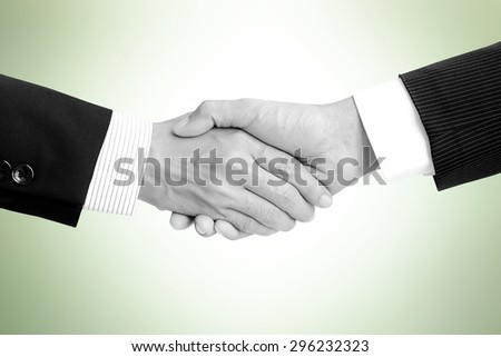 Handshake of businessmen on light green background - greeting, dealing,  merger and a acquisition concepts