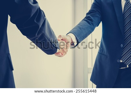 Handshake of businessmen; success, dealing & business partner concepts - vintage color effect with soft focus - stock photo