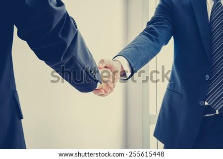 Handshake of businessmen; success, dealing & business partner concepts - vintage color effect with soft focus - stock photo
