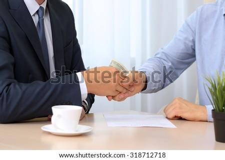 Handshake of businessmen with money - stock photo