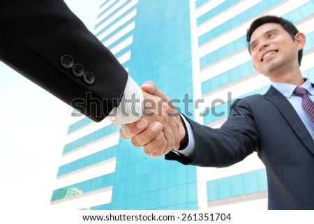 Handshake of businessmen with smiling face - greeting , dealing, merger & acquisition concepts - stock photo