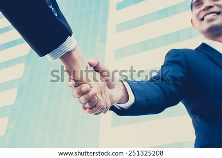 Handshake of businessmen with smiling face, greeting, dealing, partnership, merger & acquisition concepts  - vintage & retro style color effect - stock photo