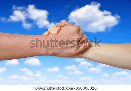 Handshake of friendship on the background blue sky - stock photo
