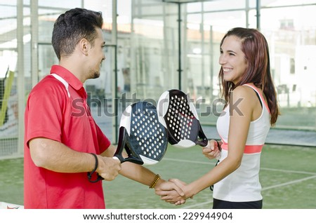 Handshake of paddle tennis players woman and man - stock photo