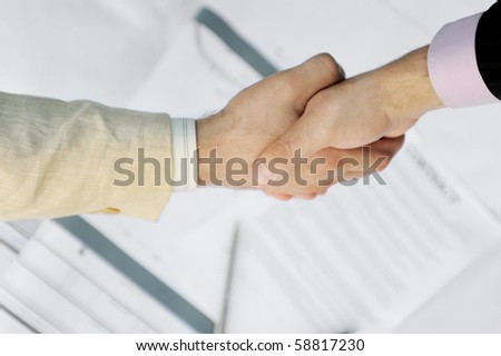 Handshake of two business partners in black and white suits - stock photo