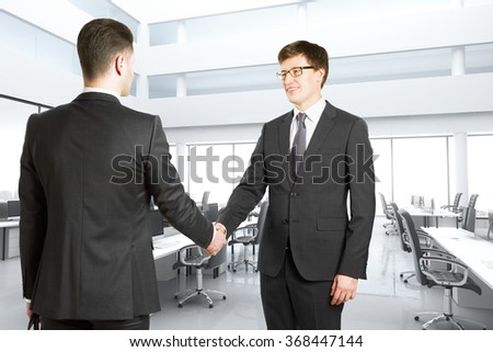 Handshake of two businessmen in a bright modern office - stock photo