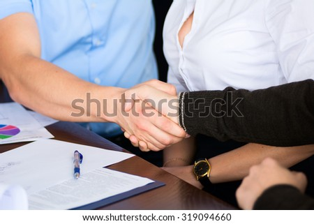 Handshake of two businessmen on the background of the Secretary of the woman after signing the contract.