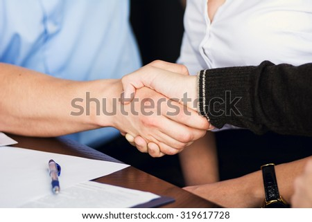 Handshake of two businessmen on the background of the Secretary of the woman after signing the contract. - stock photo