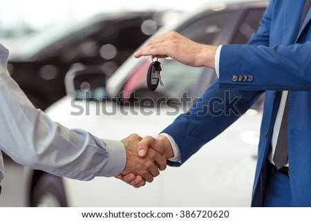 Handshake of two businessmen when selling a car in a motor show, close-up - stock photo