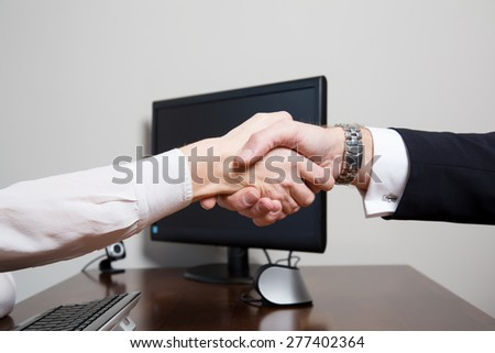 Handshake of two equal associates, sign of mutual agreement, over the wooden desk of a business office with modern equipment as desktop PC with keyboard and web camera - stock photo