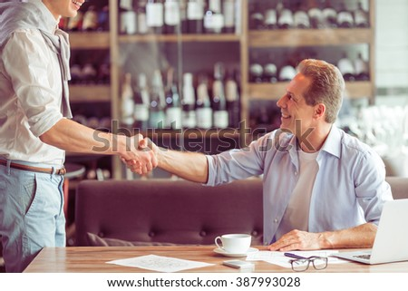 Handshake of two handsome businessmen in casual clothes meeting for working at the restaurant - stock photo