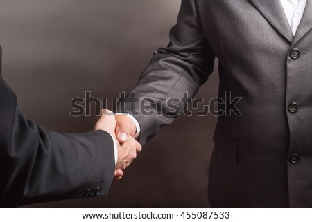 handshake of two successful businessmen on a gray background.