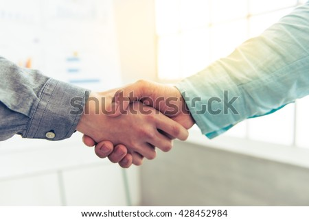 Handshake of two young businessmen, in the background is board with graphs - stock photo