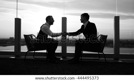 handshake of two young professionals having a business meeting talking about financial strategies