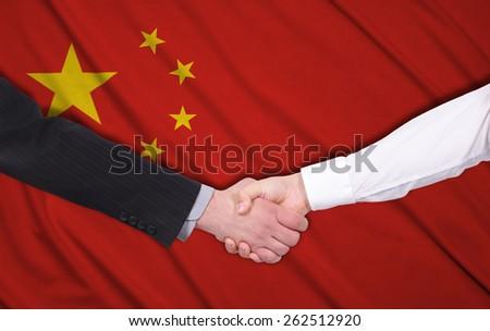handshake on a china flag background - stock photo