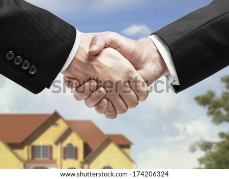 handshake on a house background - stock photo