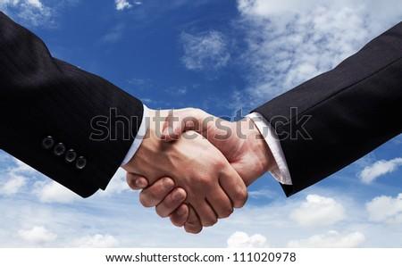 handshake on  background of sky - stock photo