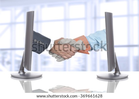 Handshake Over Desk in Business Office. Both hands are coming out of computer screens.  - stock photo