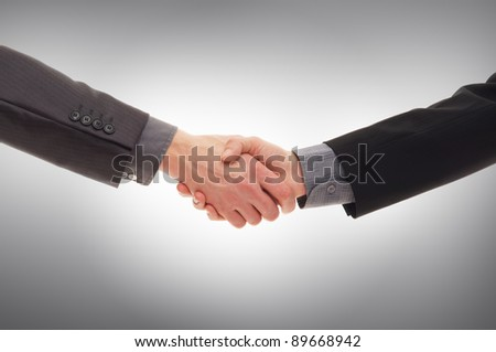Handshake over grey background - stock photo