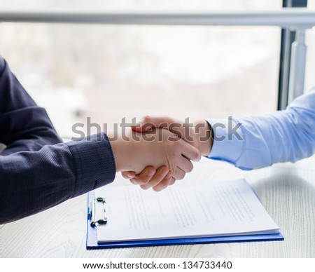 Handshake over Signed Contract - stock photo
