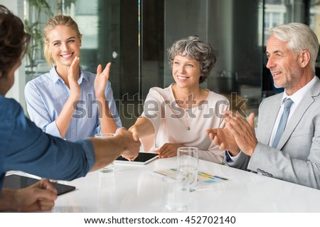 Handshake to seal a deal after a job recruitment meeting. Two successful businesspeople shaking hands in front of their colleagues. Mature businesswoman shaking hands to seal a deal. - stock photo