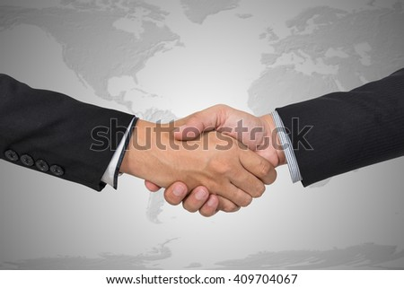 Handshake with map of the world in background, Elements of this image furnished by NASA