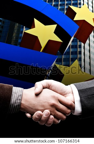 Handshake with the euro sign in the background - stock photo