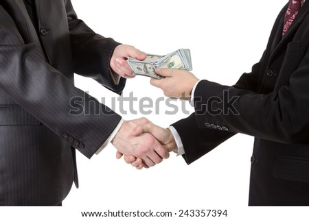 Handshake with the transfer of money from one businessman to another closeup isolated on white background - stock photo