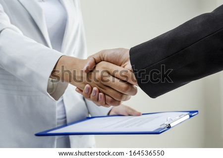 Handshaking after signing contract by businesswomen