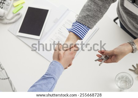 Handshaking of a real estate agent and a customer - stock photo